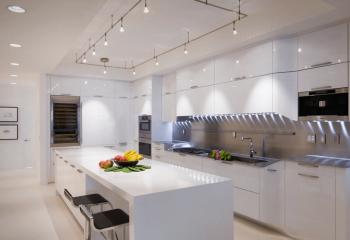 На этой фотографии кухонную зону освещает трековая система, а проход – встроенные светильники
