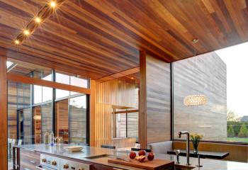Сочетание темных и светлых панелей разной длины придает динамики потолочному покрытию в современном интерьере кухни