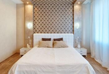 Обои с ярким рисунком помогут выделить акцентную стену и часть потолка над кроватью