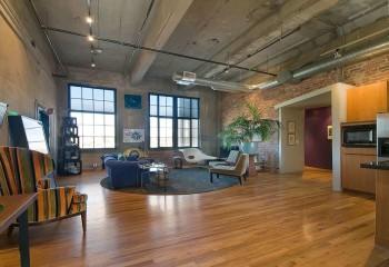 Трубы и вентканалы в комбинации с бетонными балками придают брутальности квартире студии