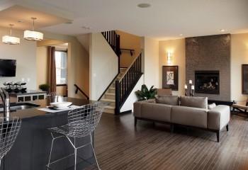 Кухня-гостиная: зона готовки визуально выделена вторым уровнем потолка, дополнительно выделенным подвесными светильниками