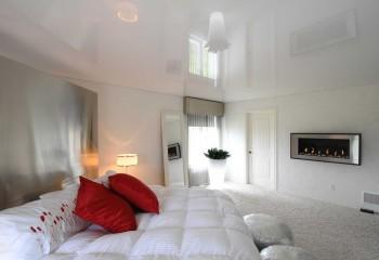Глянцевое полотно в комнатах с низкими потолками визуально дает объем