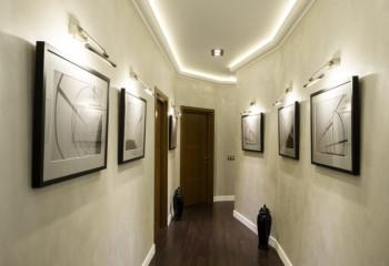 Свет от лент направлен на потолок, тогда как настенные приборы выделяют стены и картины