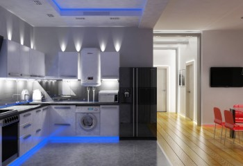 Кухня в квартире со свободной планировкой - светильники над шкафами выделяют потолок, а под ними – рабочую столешницу