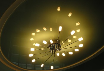 Освещение потолков натяжных: глянцевый потолок отражает свет от люстры