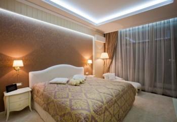 В этой спальне вообще отсутствует центральный источник света – его эффективно заменяют бра, торшер и встроенная в короб потолка светодиодная лента