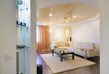 Потолок с жёлтым глянцевым полотном красиво вписан в интерьер гостиной