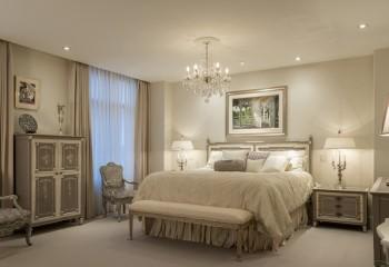 Натяжной потолок с люстрой и точечной подсветкой в спальне
