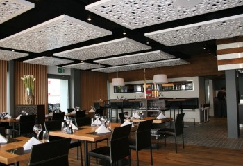 В ресторане перфорированные потолочные панели создают и нужный уровень акустики, и украшают зал