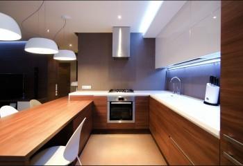 Тут использовано сразу три типа светильников: светодиодная лента отделяет потолок от белых шкафов, подвесные светильники выступают в роли разделителя на зоны, а встройка заполняет световые пропуски