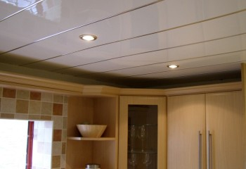 Белые глянцевые панели с серебристой каёмкой в кухне