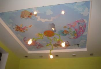 В нише на гипсокартонном потолке можно расположить тканевое натяжное полотно с рисунком на детскую тематику