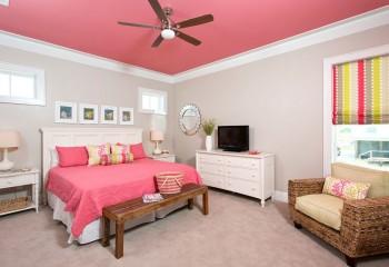 Достаточно яркий розовый потолок идеально сочетается с таким же покрывалом на кровати и занавесками