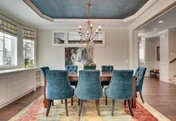 Материал на потолке органично сочетается с обивкой мягких кресел в столовой, акцентируя внимание над обеденной группой