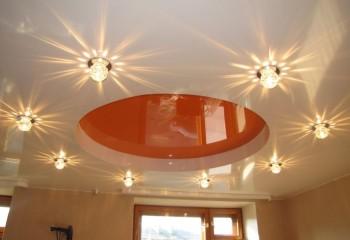 Выступающие за плоскость глянцевого потолка встраиваемые светильники подсвечивают его поверхность, создавая красивый световой рисунок