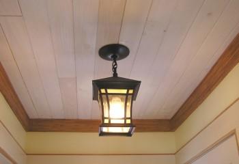 Дощатый потолок с деревянным обрамлением смотрится наиболее гармонично