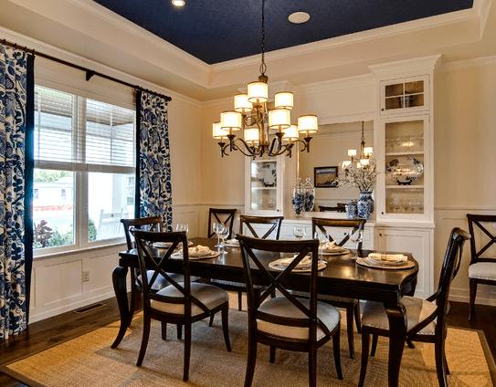 Чернильный цвет потолка подчеркивает добротную деревянную мебель
