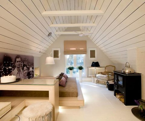 Белая вагонка в спальне на мансардном этаже зрительно увеличивает помещение