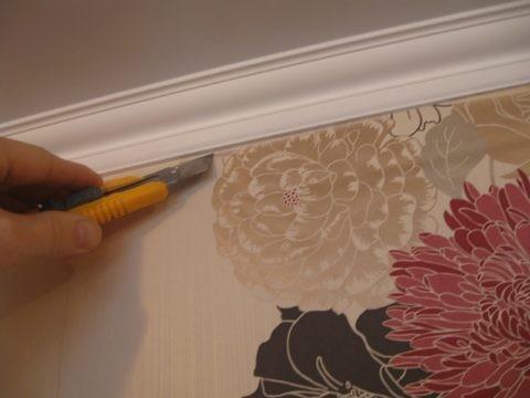 Чтобы не испортить покрытие стен, надрежьте их стык с плинтусом