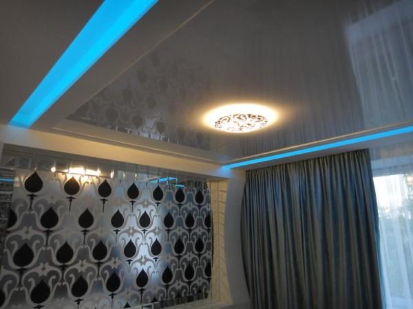 Интересное сочетание тяжёлых гардин, глянцевого натяжного потолка и скрытой диодной подсветки
