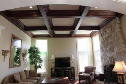 Кессонный потолок в гостиной органично сочетается с декоративным оформлением камина