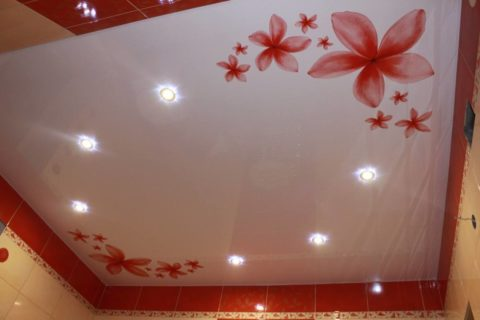 Красные цветы на натяжном полотне гармонично сочетаются с цветом кафельной плитки на стенах в ванной