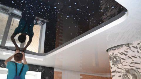 На фото - окончательная заправка плёнки двухуровневого потолка за багет шпателем