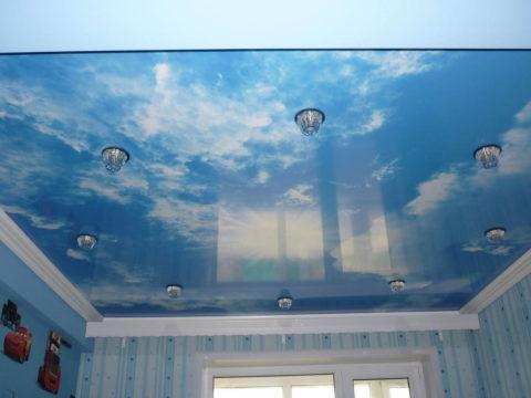 Натяжное глянцевое полотно с изображением неба зрительно увеличивает высоту комнаты