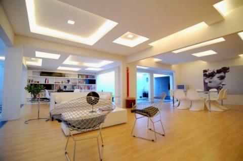 Объемная подвесная конструкция и встроенная подсветка позволяет произвести грамотное зонирование большого пространства