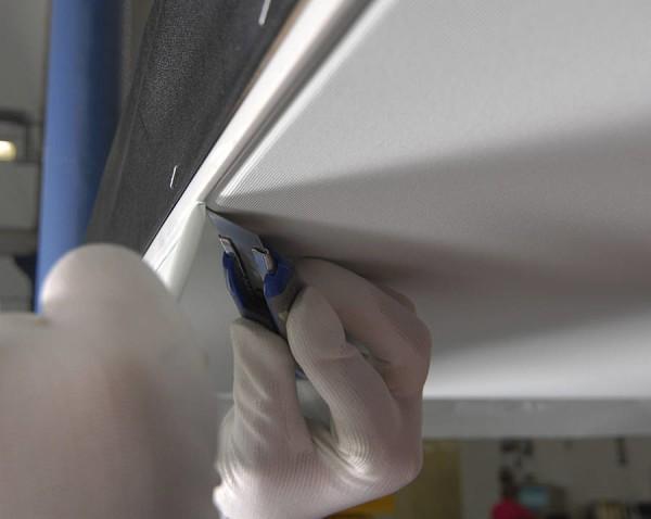 Подрезка потолочной ткани после заправки в багет