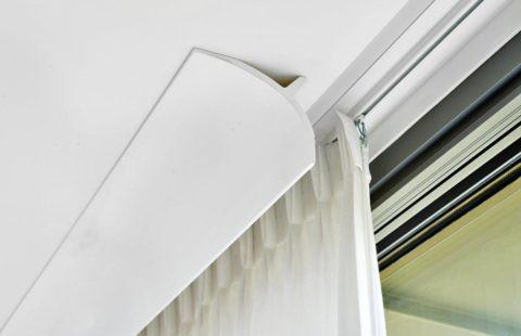 Посаженный на клей полиуретановый плинтус скрывает от зрителя карниз для штор