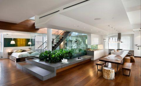 Потолок оригинальной формы с грамотным распределением осветительных приборов в апартаментах студийного типа