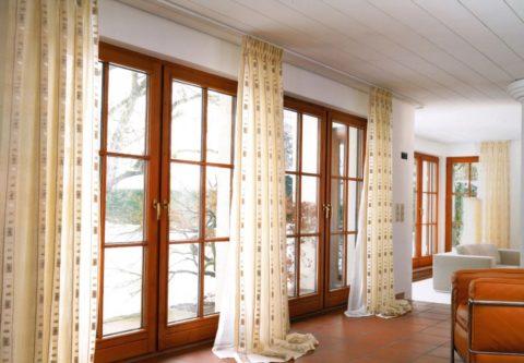 Шторный карниз закреплён на дощатом потолке, длина штор превышает высоту помещения