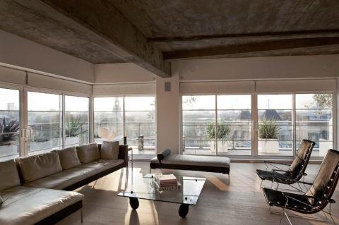Сочетание серой и черной мебели с потолком из бетона