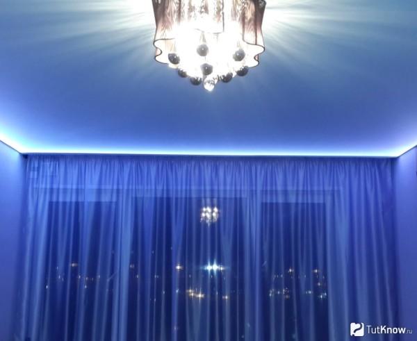 Сочетание синих лёгких занавесей и голубого натяжного полка в тандеме со скрытой, светодиодной подсветкой