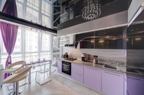 Сочетание угольно-серого цвета натяжного глянцевого полотна с нежными фиалковыми и бежевыми оттенками на кухне