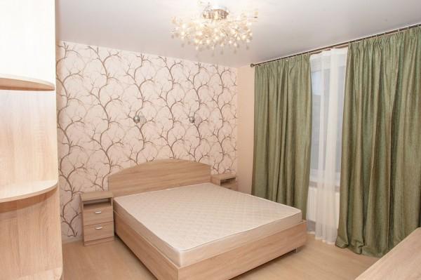 Тяжёлые гардины фисташкового оттенка в сочетании с матовым натяжным потолком в интерьере спальни