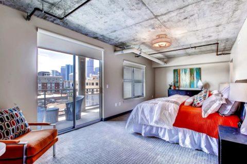 Яркий текстиль и декор на фоне бетона позволяют создать динамичный современный интерьер